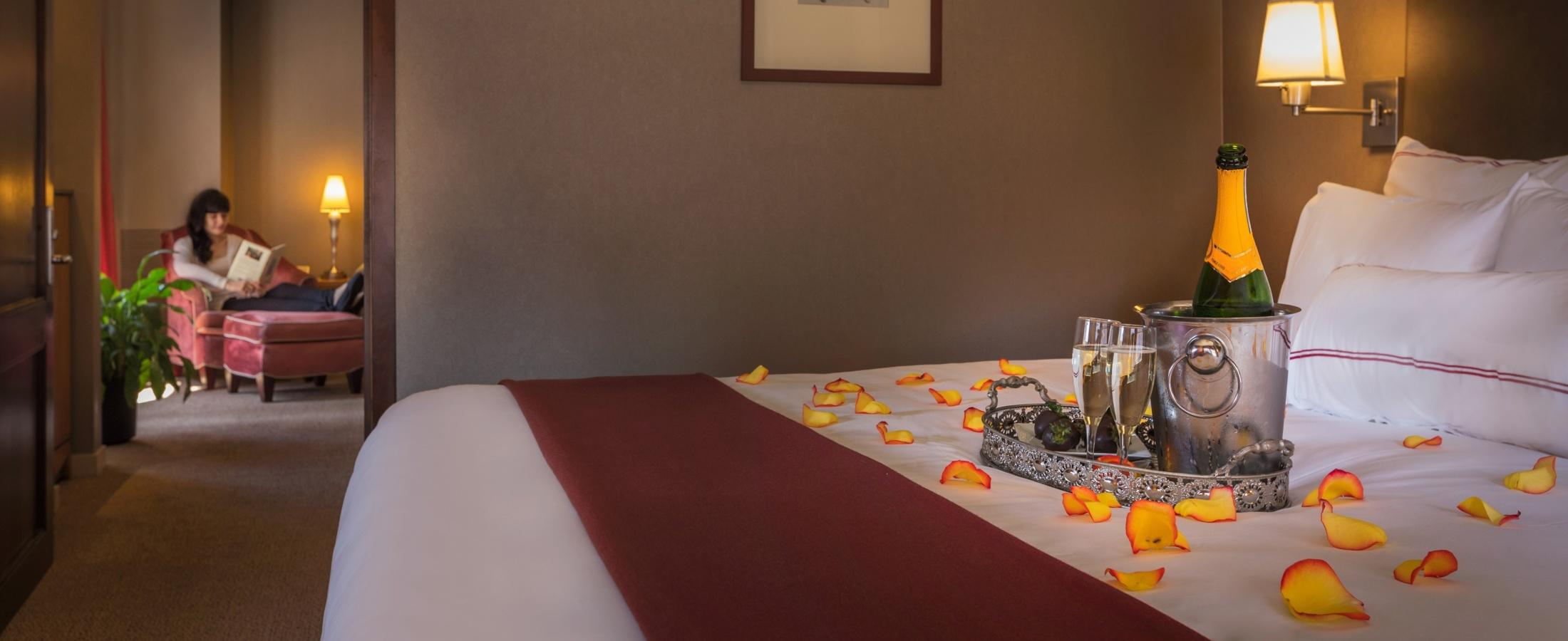 Rose petals, prosecco and chocolate strawberries set up on bed