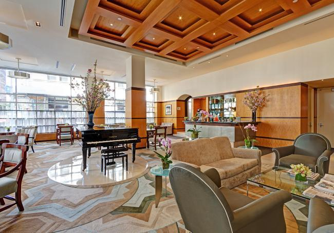 Grand Lobby with plenty of seating, tables, floor-to-ceiling windows, and a grand piano.